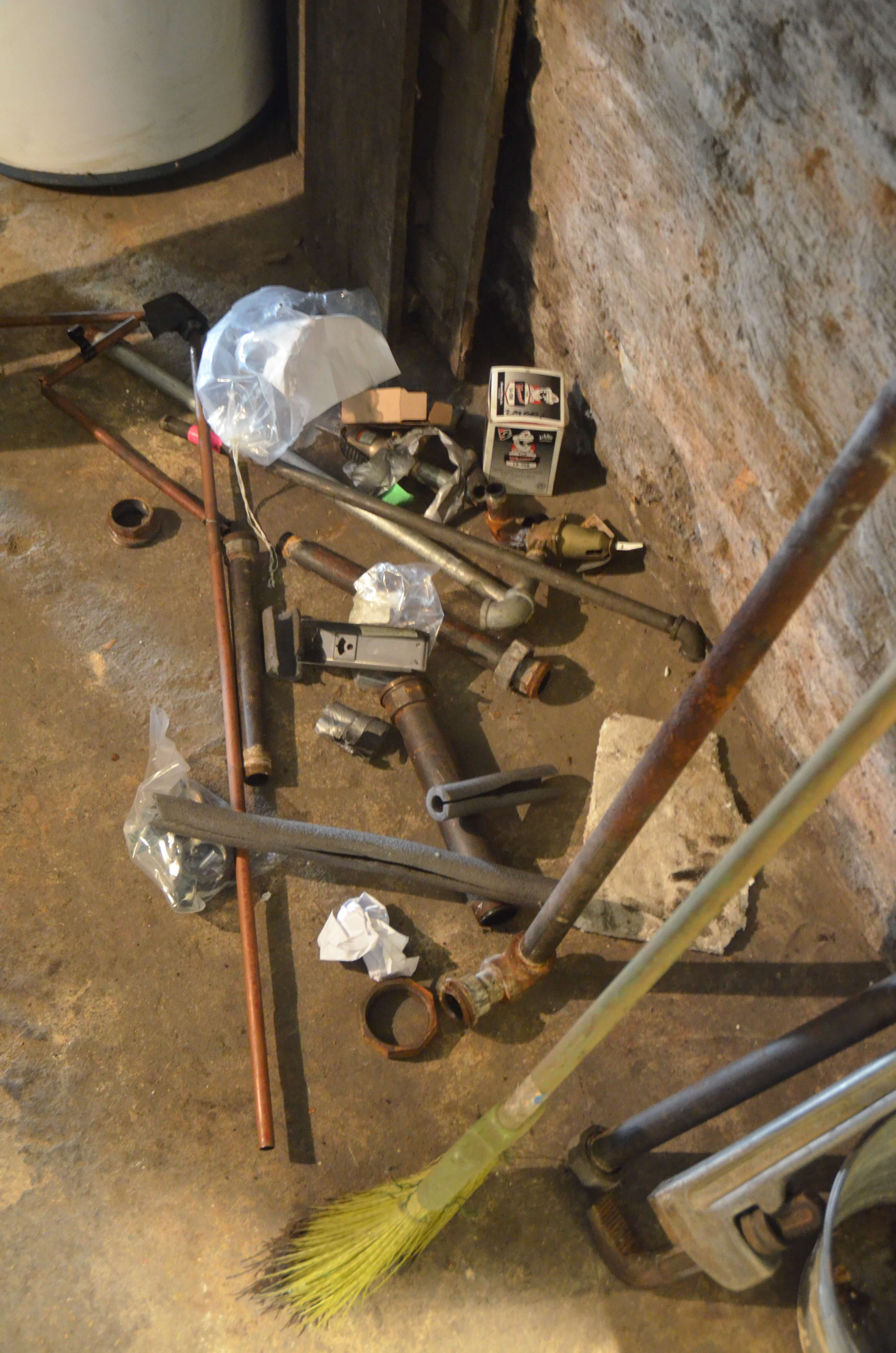 Plumbing parts litter the basement as the new boiler is installed!